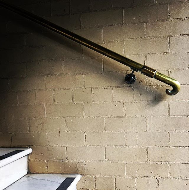 beautiful-brass-handle-finial-floating-against-textured-brick-and-bianco-carrara-steps-mark-the-begi